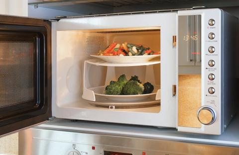 On y voit un micro-ondes dont la porte est ouverte, avec à l'intérieur deux plats superposés à l'aide d'un accessoire