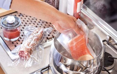 On y voit une main déposer dans une eau bouillonnante un morceau de saumon dans un sachet sous vide