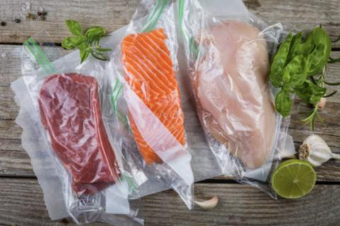 Ony voit une pièce de boeuf, une pièce de saumon et un morceau de poulet, tous trois dans des sachets sous vide