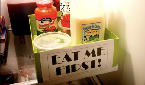Boite de couleur dans un frigo avec une étiquette EAT ME FIRST