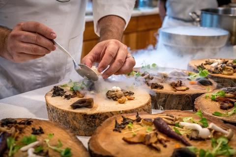 Chef cuisinier en train de déposer sa préparation sur des assiettes en rondin de bois
