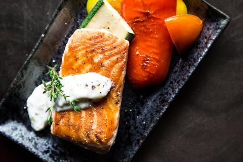 on y voit une saumon cuit avec des légumes bien présentés dans une assiette noire