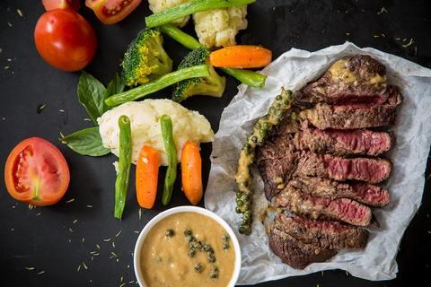 C'est une assiette avec une viande de boeuf découpées et cuisinées, accompagnées de carottes, tomates et salade