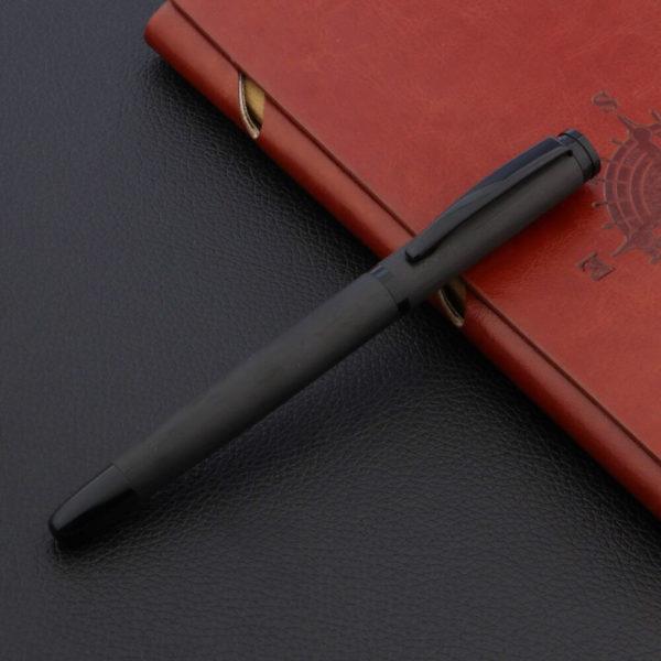 Stylo à bille en titane noir avec le capuchon détaché posé sur un carnet brun et un support noir