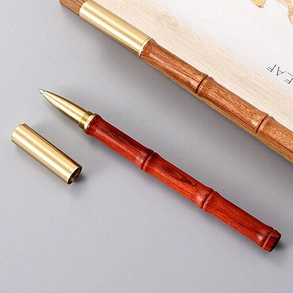 Stylo à bille en bambou et doré posé sur du bois et un support blanc
