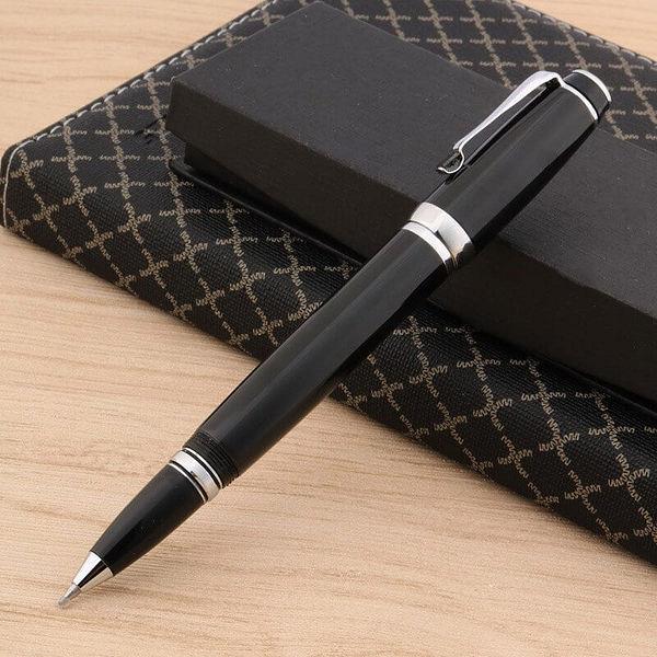 Stylo roller noir compact avec le capuchon détaché posé sur un carnet brun