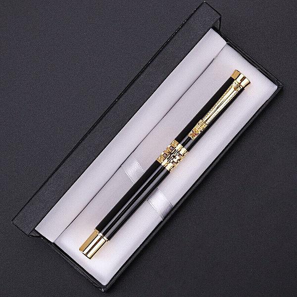 Stylo à bille motif dragon doré et noir posé sur un support blanc. Le stylo est dans sa boite.