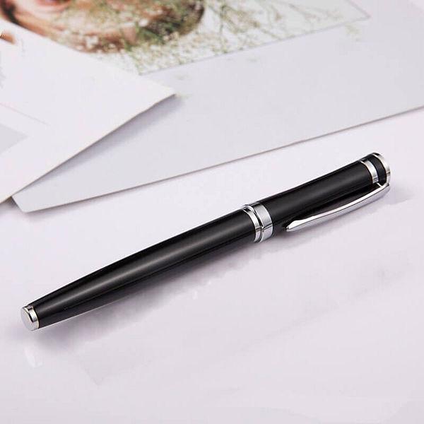 Stylo à plume en métal posé sur une boite noire et un support blanc