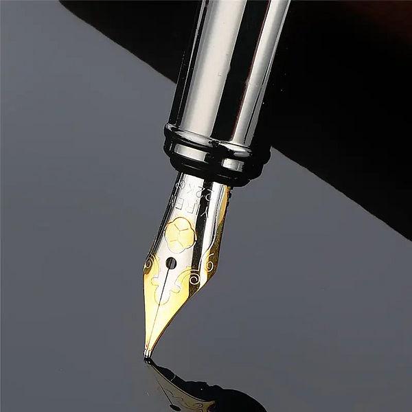 Stylo à plume argenté brillant avec le capuchon détaché posé sur un carnet brun