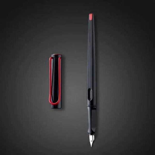 Stylo à plume noir et rouge avec le capuchon détaché sur fond noir