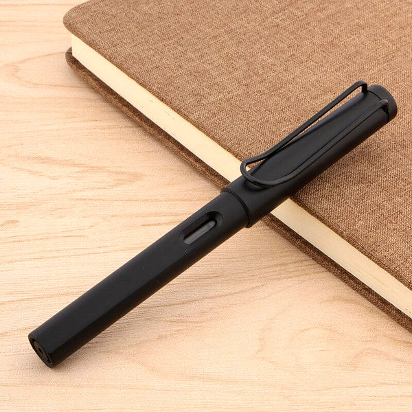 Stylo à plume noir mat posé sur un carnet brun et un support en bois