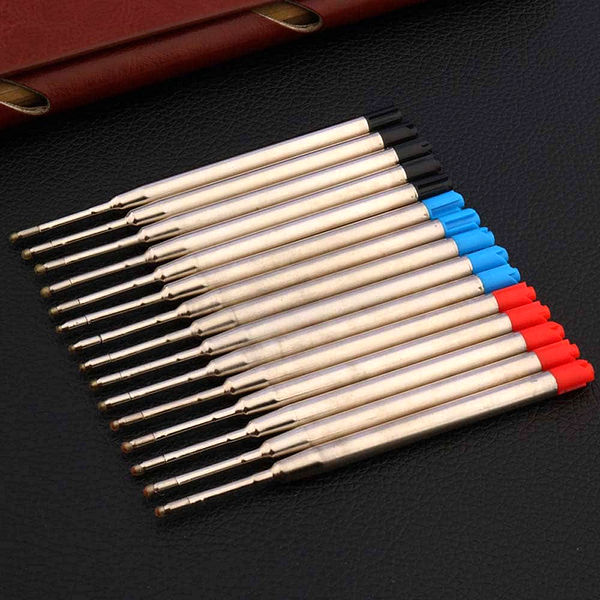 Recharges de stylo bille de différentes couleurs posé sur un carnet brun et sur un support noir