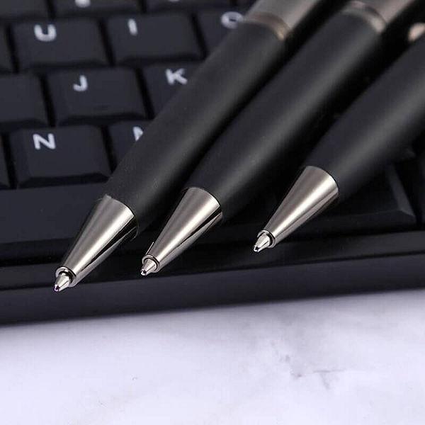 Stylo à bille en caoutchouc noir et gris posé sur un ordinateur qui est lui même posé sur une table en marbre