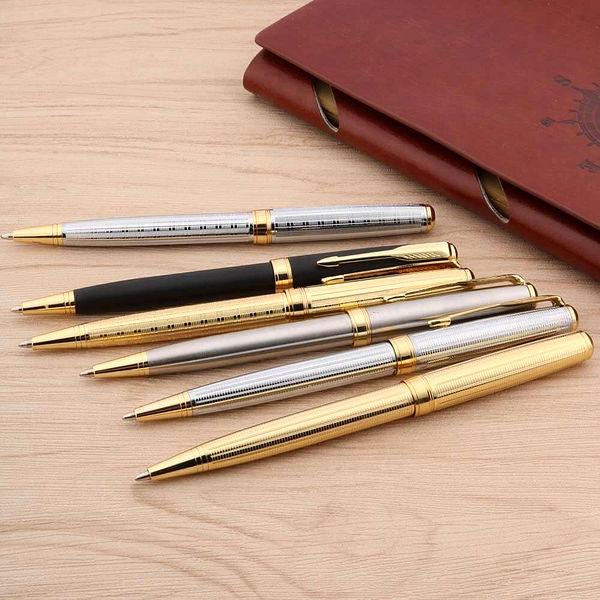 Stylo à bille classique doré et argenté posé sur un carnet brun
