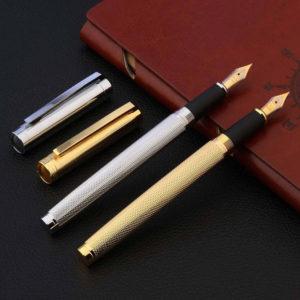 Stylo à plume moderne doré et argenté avec le capuchon détaché posé sur un carnet brun et un support noir