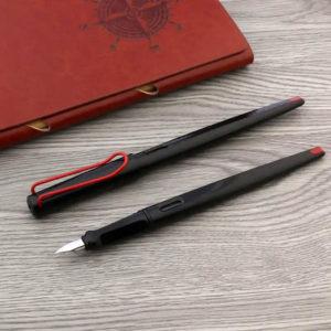 Un stylo plume long noir et rouge sur un support en bois à côté d'un carnet brun