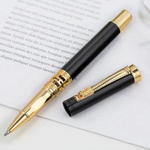Stylo à bille motif dragon doré et noir posé sur un support blanc