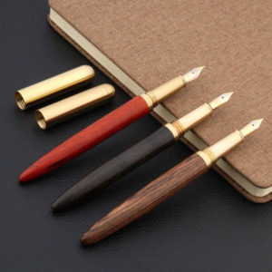 Stylo à plume en bois et doré très élégant posé sur un carnet brun avec le capuchon détaché
