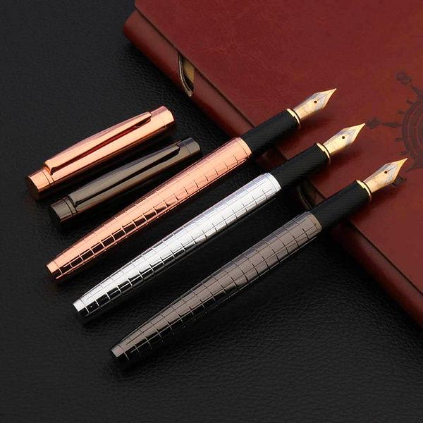 Stylo à plume en cuivre brillant avec le capuchon détaché posé sur un carnet brun et un support noir