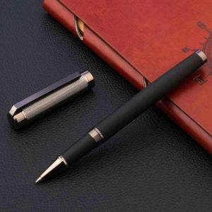 Stylo à bille en carbone noir et brun posé sur un carnet brun et un support noir