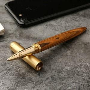 Stylo à bille en bois et doré avec le capuchon détaché posé sur une table grise avec un téléphone portable