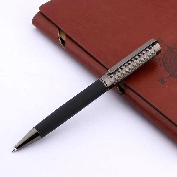 Stylo à bille en carbone noir et gris posé sur un carnet brun et un support blanc