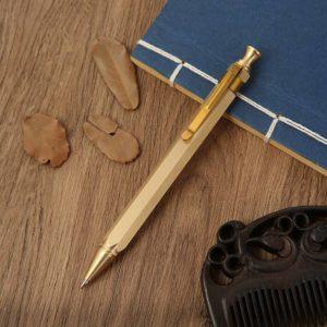 stylo à bille doré de luxe sur un support en bois