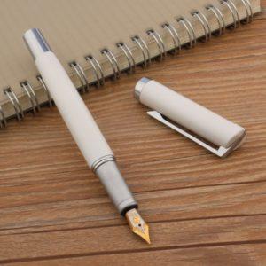 stylo plume avec plume argentée et dorée sur un support en bois