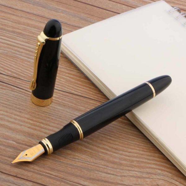 stylo plume épais avec une plume doré sur un support en bois