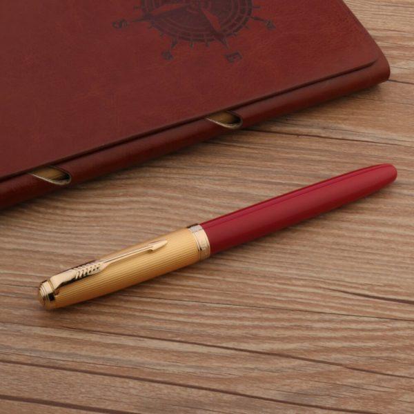 stylo à plume rouge de luxe sur un support en bois
