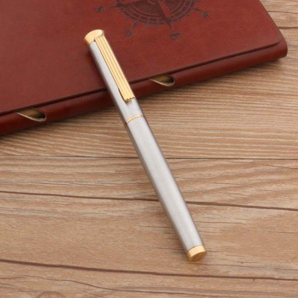 stylo à plume doré vintage sur un support en bois