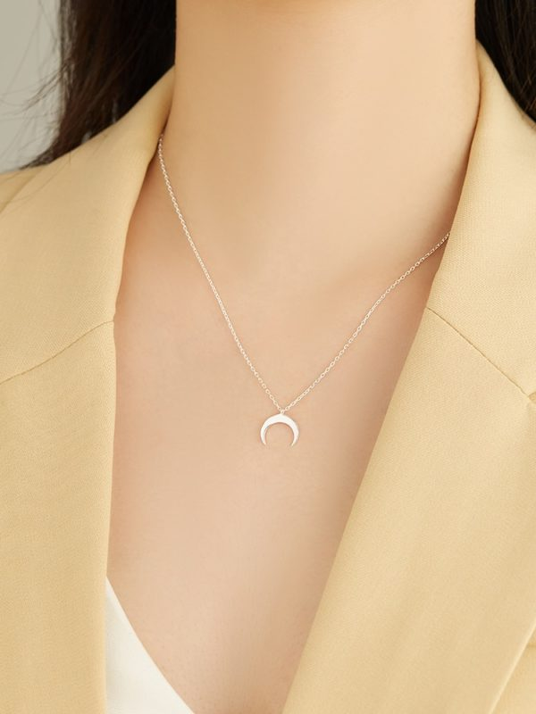 Collier croissant de lune argent porté par une femme